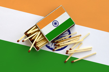 India flag  is shown on an open matchbox, from which several matches fall and lies on a large flag.