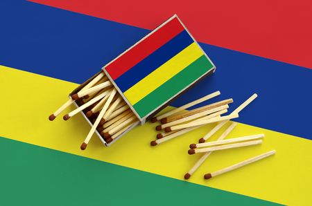 Mauritius flag  is shown on an open matchbox, from which several matches fall and lies on a large flag.