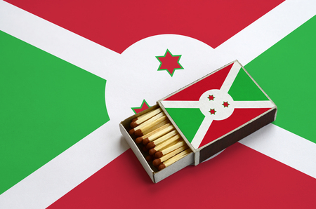 Burundi flag  is shown in an open matchbox, which is filled with matches and lies on a large flag.