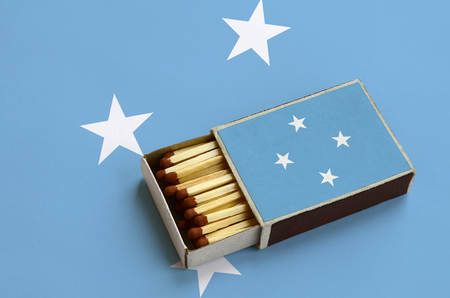 Micronesia flag  is shown in an open matchbox, which is filled with matches and lies on a large flag.