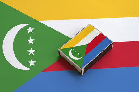 Comoros flag  is pictured on a matchbox that lies on a large flag.