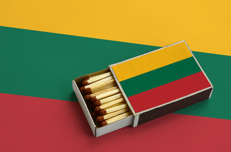 Lithuania flag is shown in an open matchbox, which is filled with matches and lies on a large flag. Stock fotó