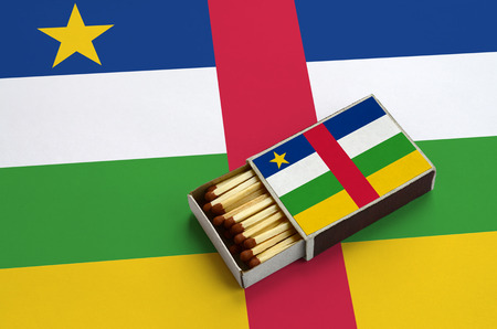 Central African Republic flag  is shown in an open matchbox, which is filled with matches and lies on a large flag.
