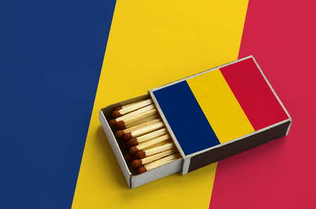 Chad flag  is shown in an open matchbox, which is filled with matches and lies on a large flag.