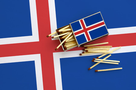Iceland flag  is shown on an open matchbox, from which several matches fall and lies on a large flag.