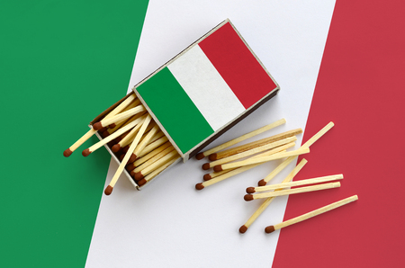 Italy flag  is shown on an open matchbox, from which several matches fall and lies on a large flag.