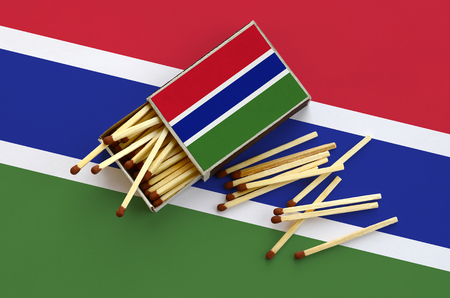 Gambia flag  is shown on an open matchbox, from which several matches fall and lies on a large flag. Stock Photo