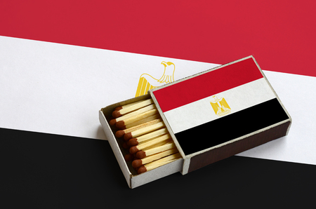 Egypt flag  is shown in an open matchbox, which is filled with matches and lies on a large flag. Banco de Imagens