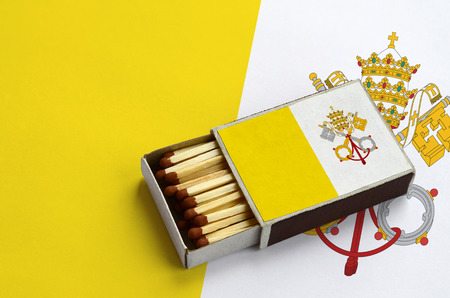 Vatican City State flag  is shown in an open matchbox, which is filled with matches and lies on a large flag. Stock Photo