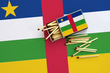 Central African Republic flag  is shown on an open matchbox, from which several matches fall and lies on a large flag.