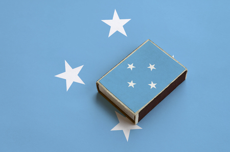 Micronesia flag  is pictured on a matchbox that lies on a large flag. Stock Photo