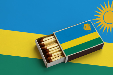 Rwanda flag is shown in an open matchbox, which is filled with matches and lies on a large flag.