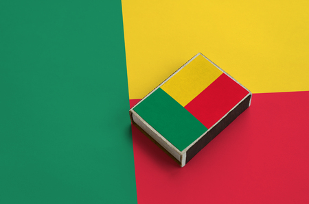 Benin flag  is pictured on a matchbox that lies on a large flag.