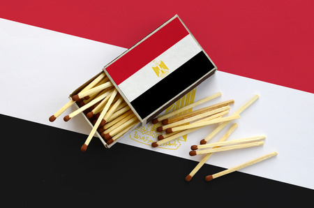 Egypt flag  is shown on an open matchbox, from which several matches fall and lies on a large flag.