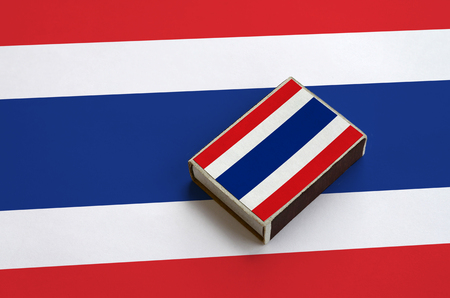 Thailand flag is pictured on a matchbox that lies on a large flag.