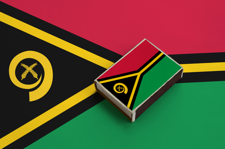 Vanuatu flag  is pictured on a matchbox that lies on a large flag. Banco de Imagens
