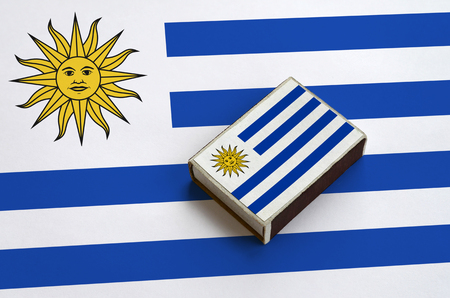Uruguay flag  is pictured on a matchbox that lies on a large flag.
