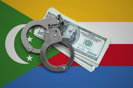 Comoros flag  with handcuffs and a bundle of dollars. Currency corruption in the country. Financial crimes. 版權商用圖片