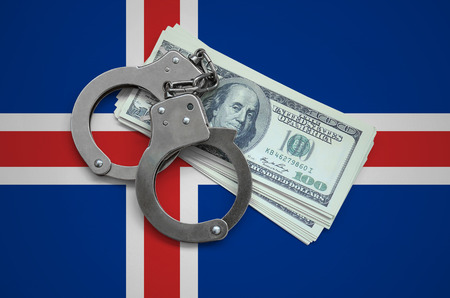 Iceland flag  with handcuffs and a bundle of dollars. Currency corruption in the country. Financial crimes.