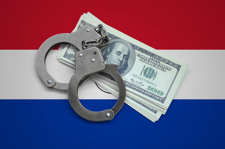 Paraguay flag  with handcuffs and a bundle of dollars. Currency corruption in the country. Financial crimes.