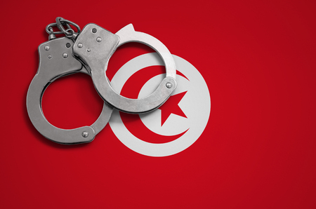 Tunisia flag  and police handcuffs. The concept of crime and offenses in the country.