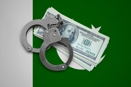 Pakistan flag  with handcuffs and a bundle of dollars. Currency corruption in the country. Financial crimes. 版權商用圖片