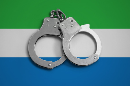 Sierra Leone flag  and police handcuffs. The concept of observance of the law in the country and protection from crime.