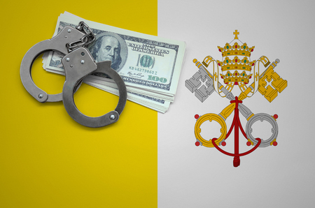 Vatican City State flag  with handcuffs and a bundle of dollars. The concept of breaking the law and thieves crimes.