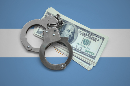 Argentina flag  with handcuffs and a bundle of dollars. Currency corruption in the country. Financial crimes. 스톡 콘텐츠