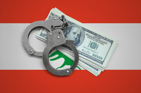 Lebanon flag  with handcuffs and a bundle of dollars. Currency corruption in the country. Financial crimes.