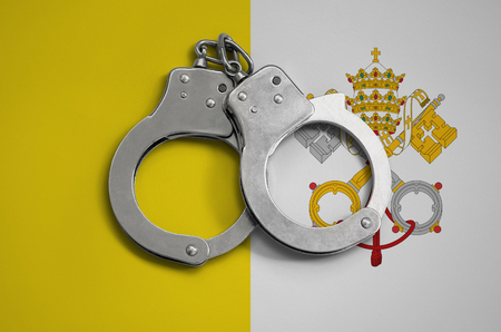 Vatican City State flag  and police handcuffs. The concept of observance of the law in the country and protection from crime.