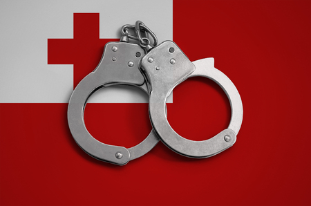 Tonga flag  and police handcuffs. The concept of observance of the law in the country and protection from crime. Stock Photo