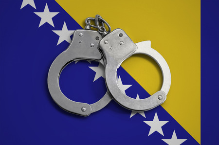 Bosnia and Herzegovina flag  and police handcuffs. The concept of observance of the law in the country and protection from crime. Stock Photo