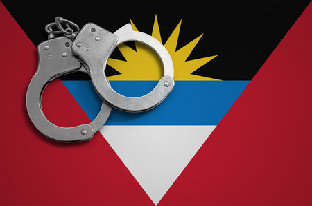Antigua and Barbuda flag  and police handcuffs. The concept of crime and offenses in the country.