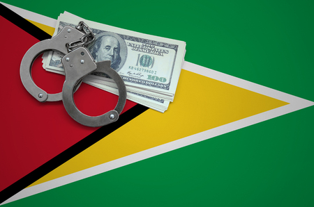 Guyana flag with handcuffs and a bundle of dollars. The concept of breaking the law and thieves crimes.