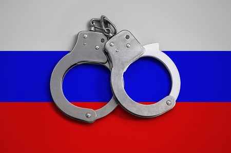 Russia flag  and police handcuffs. The concept of observance of the law in the country and protection from crime. Stock Photo