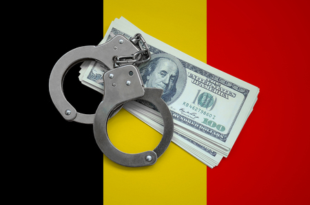 Belgium flag  with handcuffs and a bundle of dollars. Currency corruption in the country. Financial crimes.