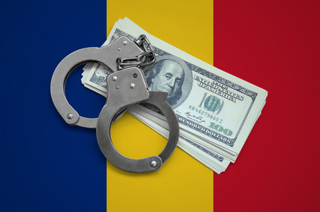 Romania flag  with handcuffs and a bundle of dollars. Currency corruption in the country. Financial crimes.