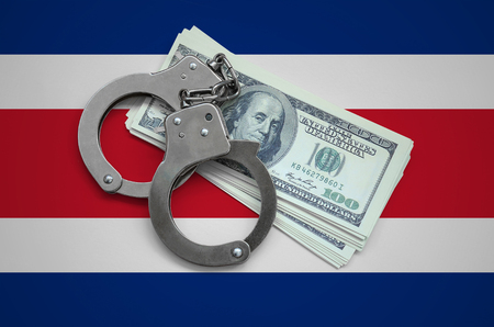 Costa Rica flag  with handcuffs and a bundle of dollars. Currency corruption in the country. Financial crimes.