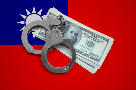 Taiwan flag  with handcuffs and a bundle of dollars. Currency corruption in the country. Financial crimes.