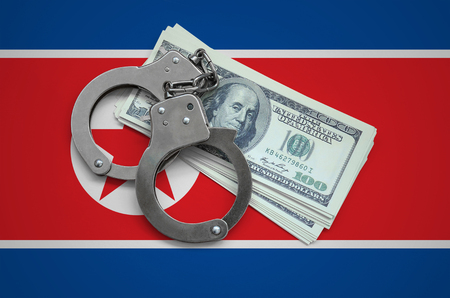 North Korea flag  with handcuffs and a bundle of dollars. Currency corruption in the country. Financial crimes. Фото со стока