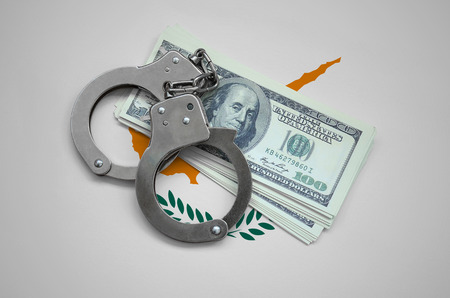 Cyprus flag  with handcuffs and a bundle of dollars. Currency corruption in the country. Financial crimes.