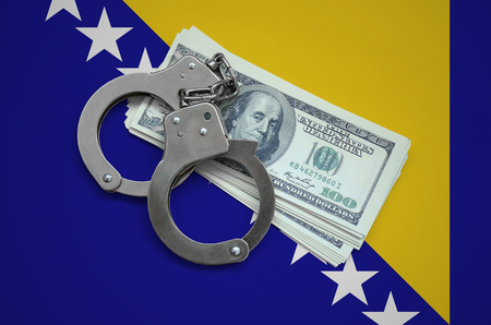 Bosnia and Herzegovina flag  with handcuffs and a bundle of dollars. Currency corruption in the country. Financial crimes. 版權商用圖片
