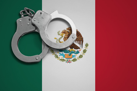 Mexico flag  and police handcuffs. The concept of crime and offenses in the country.