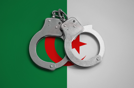 Algeria flag  and police handcuffs. The concept of observance of the law in the country and protection from crime. Stock Photo