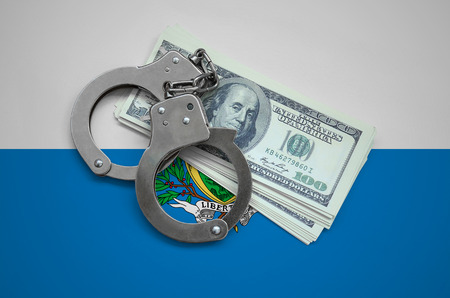 San Marino flag  with handcuffs and a bundle of dollars. Currency corruption in the country. Financial crimes.
