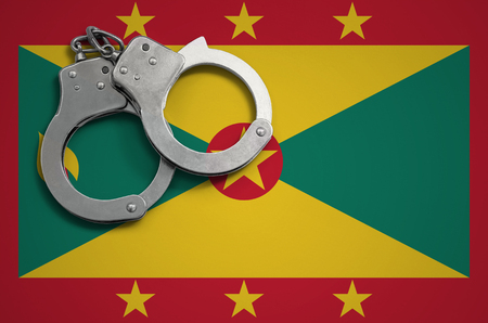 Grenada flag  and police handcuffs. The concept of crime and offenses in the country. Reklamní fotografie