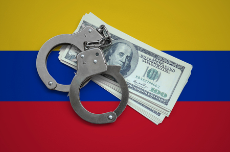Venezuela flag  with handcuffs and a bundle of dollars. Currency corruption in the country. Financial crimes.