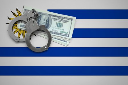 Uruguay flag  with handcuffs and a bundle of dollars. The concept of breaking the law and thieves crimes.