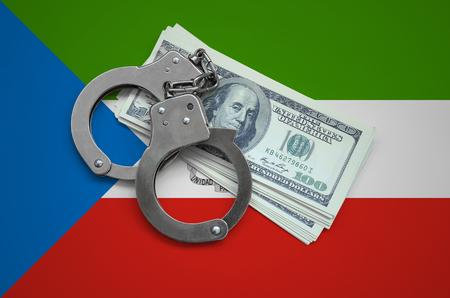 Bandera de Guinea Ecuatorial con esposas y un paquete de dólares. Corrupción monetaria en el país. Delitos económicos. Foto de archivo
